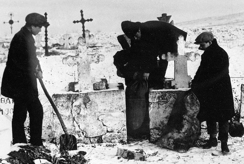 Комсомольцы извлекают зерно, спрятанное кулаками на кладбище