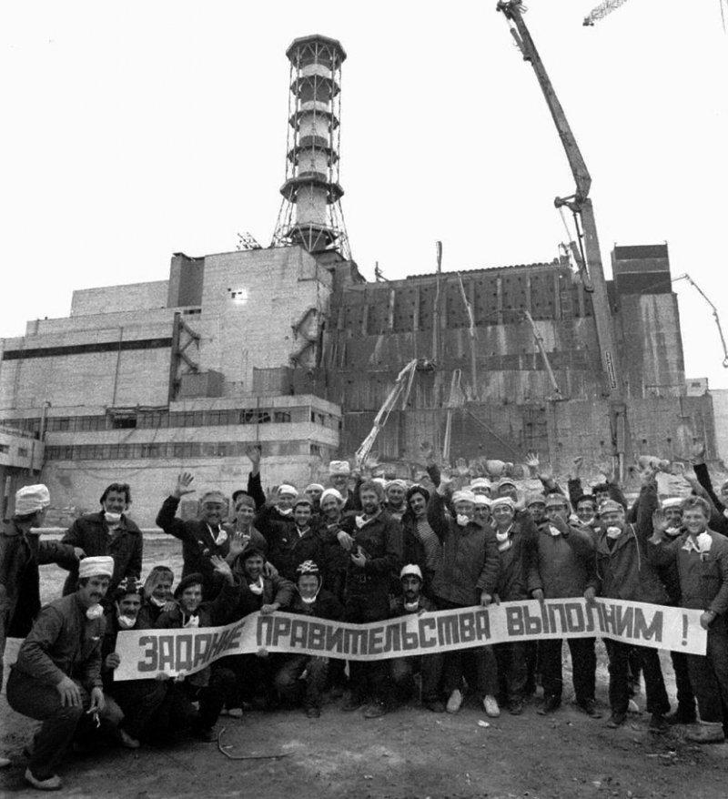 Рабочие на фоне недостроенного бетонного саркофага над Чернобыльским реактором
