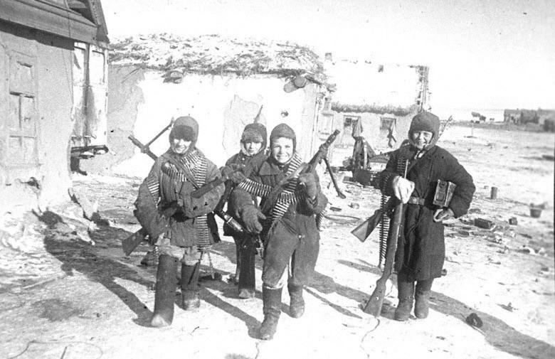 Дети собирают брошенное немцами оружие